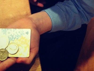 child holding money and pktmny card