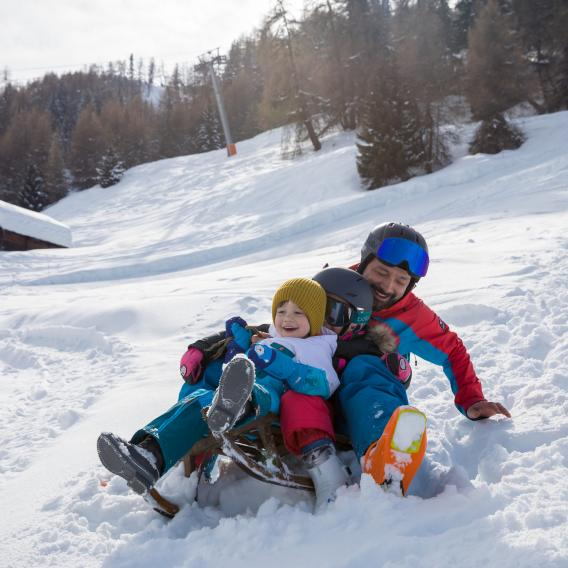 Father and child riding a bobsleigh in La Plagne ski resort France
